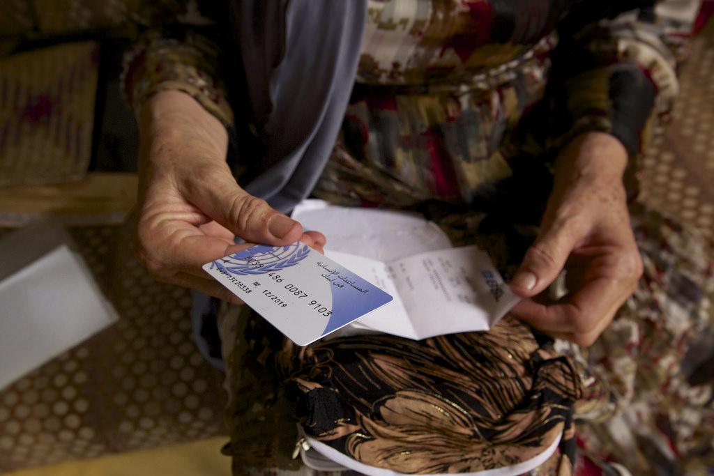 """I rifugiati siriani sono rappresentati dai media libanesi come """"opportunisti"""" che beneficiano degli aiuti internazionali. Nella foto una rifugiata ha in mano la carta consegnatale da UNHCR, attraverso la quale potrà usufruire di un piccolo budget mensile per provvedere alle necessità fondamentali. Fornire denaro - e non direttamente i beni - consente di immettere quei soldi nell'economia locale. ©UNHCR/S.Hoibak"""