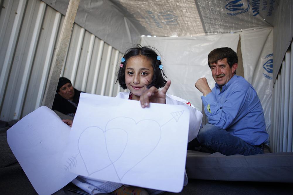 Solaf, rifugiata siriana, disegna nel caravan dove vive con suo fratello e i suoi genitori nel campo per rifugiati di Azraq, in Giordania. Quello che le manca di più della Siria è suo nonno. ©UNHCR/A.Sakkab