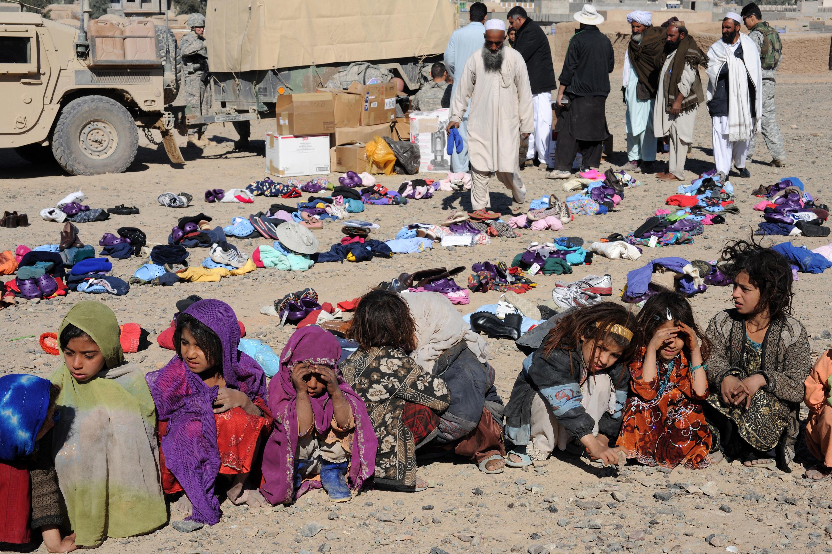 Bambine afgane in un campo per sfollati interni, attendono la distribuzione degli abiti per l'inverno (2010).